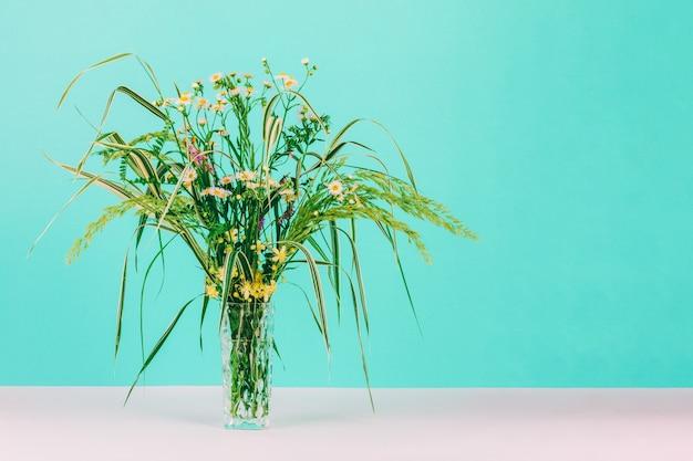Sommerblumenstrauß von grünen kräutern und von kamillenblumen in einem glasvase auf einem tadellosen pastellhintergrund mit kopienraum