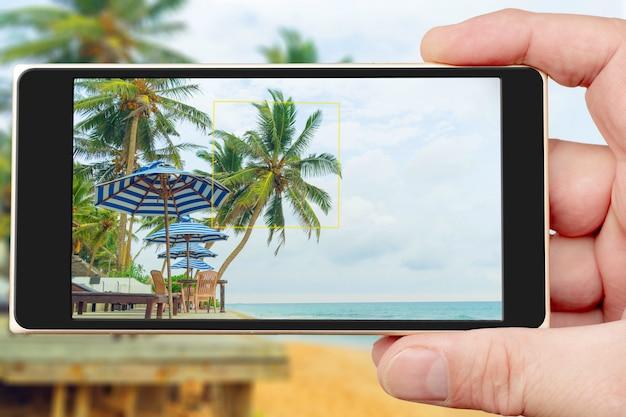 Sommercafé durch ozean auf smartphonebildschirm. sonniger tag in den tropen.