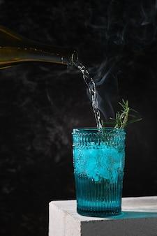 Sommercocktail mit eis, limette und rosmarin mit rauch auf weißem betonständer