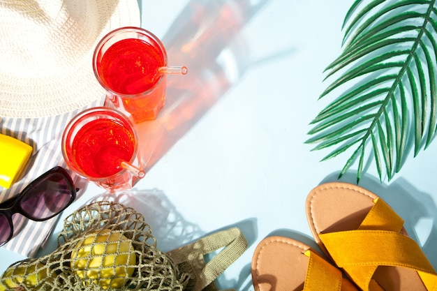 Sommercocktail mit grünen äpfeln im netzbeutel, sonnenbrille, schuhe und hut