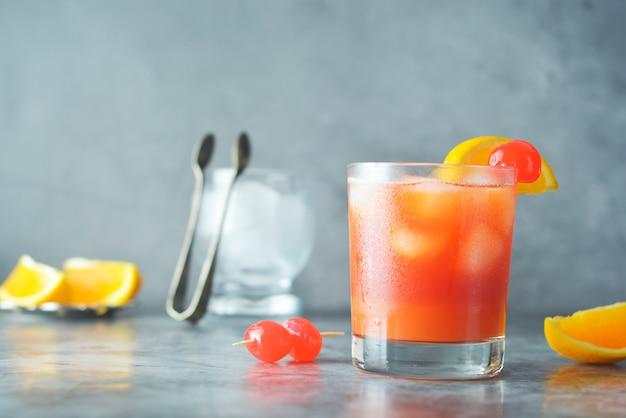 Sommercocktail. orangensaft mit minze, spritze, fruchtscheiben und kirsche mit eis.