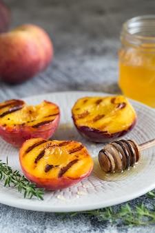 Sommerdessert: reife gegrillte pfirsiche mit honig kochen