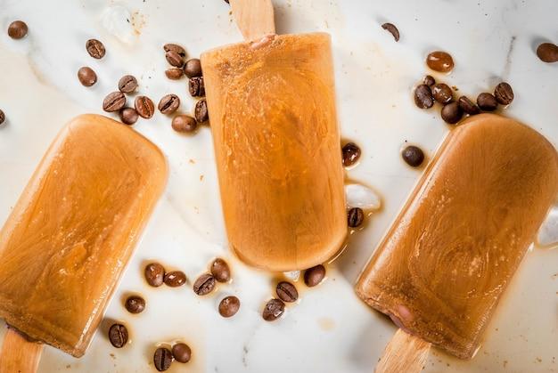 Sommerdesserts. gefrorene getränke. süßes eis am stiel aus kaffee und milch. in kaffeetassen auf einem weißen marmortisch mit kaffeebohnen. ansicht von oben