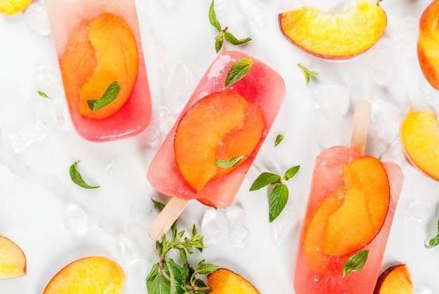 Sommerdesserts. gefrorene getränke. süßes fruchteis am stiel aus gefrorenem pfirsichtee mit minze. auf einem weißen marmortisch mit zutaten - pfirsiche, minze, eis. kopieren sie platz