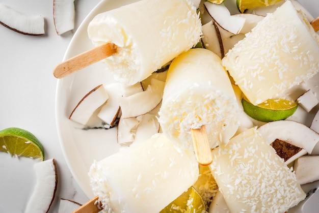 Sommerdesserts. vegane diätkost. eis am stiel der kokosnuss- und kalkhauptfrucht