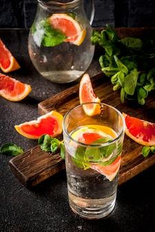 Sommererfrischungs-detoxwassergetränk mit rosa pampelmuse und frischer minze