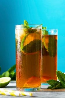 Sommererfrischungsgetränk, zwei gläser mit gefrorenem früchtetee mit minzblättern und limette.