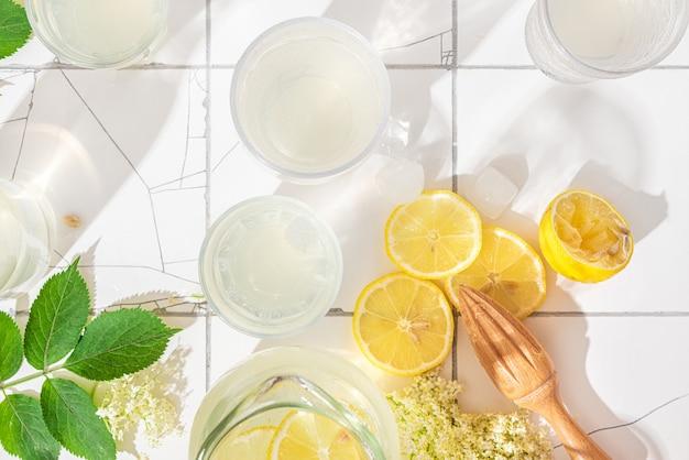 Sommererfrischungsmocktail mit zitronen, holunderblüten und eiswürfeln in gläsern auf weißer oberfläche mit hartem licht
