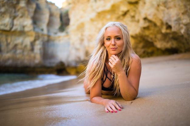 Sommererholungs- und reisekonzept. schönes gebräuntes junges modemodell im bikini, der an der seeküste aufwirft. frau im badeanzug der strandkleidung mit nassem haar und körper, die auf einem strand liegen