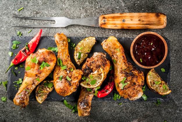 Sommeressen. ideen zum grillen, grillparty. hähnchenschenkel, flügel gegrillt, in flammen gebraten. mit scharfem chili, zitrone und bbq-sauce. dunkler steintisch. kopieren sie die draufsicht des raumes