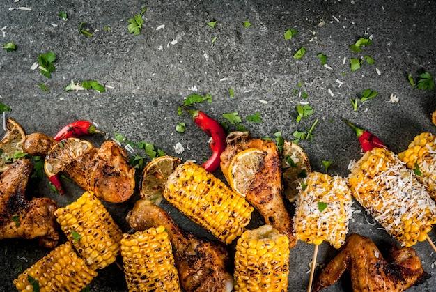 Sommeressen. ideen zum grillen, grillparty. mais und huhn (beine, flügel) gegrillt, auf feuer gebraten. mit einer prise käse (eloten), paprika, zitrone. dunkler steintisch. kopieren sie die draufsicht des raumes