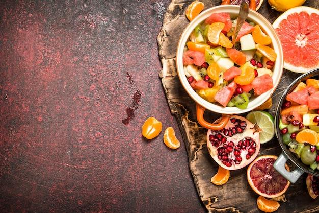 Sommeressen. tropischer salat aus exotischen früchten. auf rustikalem hintergrund.