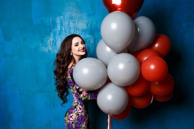 Sommerferien, feier und lifestyle-konzept - schöne frau mit bunten luftballons im studio. schickes make-up, leuchtend rote lippen, weißes lächeln