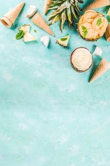 Sommerferien-ferienkonzept, stellte verschiedene tropische eissorbets, gefrorene säfte in der ananas, in der pampelmuse und in der kokosnuss, hellblaue konkrete tabelle ein