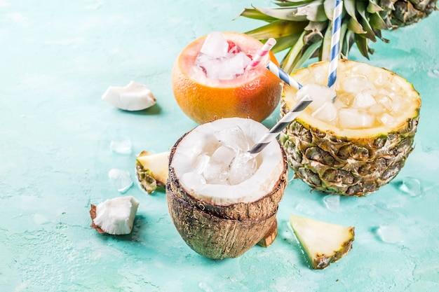 Sommerferien-getränkekonzept stellte verschiedene tropische cocktails oder säfte in der ananaspampelmuse und -kokosnuss mit eis ein
