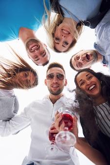 Sommerferien, glückliche menschen - eine gruppe von teenagern, die mit einem glücklichen lächeln im gesicht nach unten schauen.
