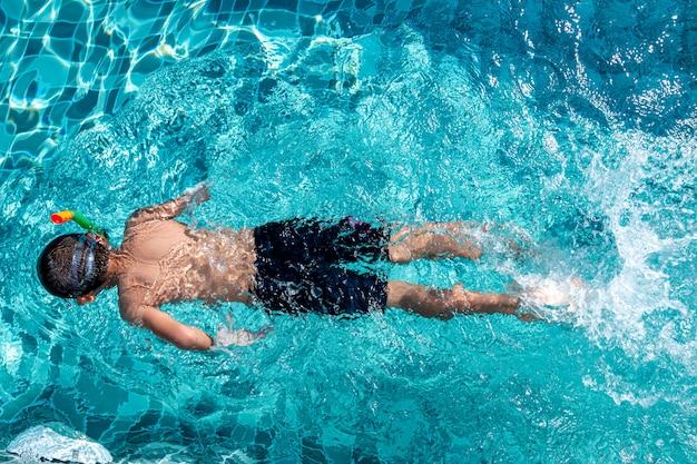 Sommerferien - glücklicher junge in den gesichtsmasken und in den schnorcheln im swimmingpool.