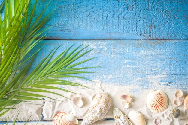 Sommerferien hintergrund. alter blauer hölzerner plankentisch mit muschel, seestern und strandsand