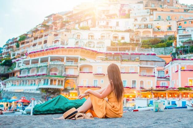 Sommerferien in italien. junge frau im positano-dorf auf dem hintergrund, amalfiküste, italien