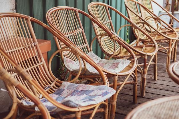 Sommerferien-konzept: braune stühle der hölzernen webart und tabellenplatz auf straßenrestaurant