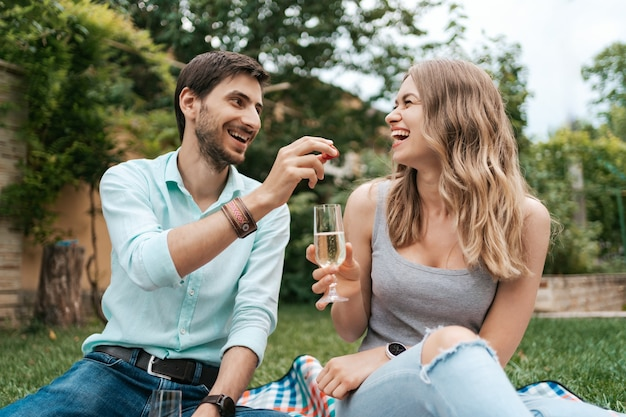 Sommerferien, menschen, romantik, mann und frau füttern sich gegenseitig mit erdbeeren, trinken sekt und genießen die gemeinsame zeit zu hause