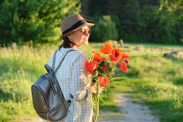 Sommerferien, naturreise, reife schöne frau, die entlang landstraße mit blumenstrauß von mohnblumen, landschaftlich reizvoller landschaftssonnenuntergangsraum, kopienraum geht