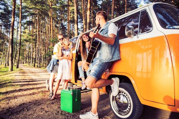 Sommerferien, roadtrip, urlaub, reisen und menschen konzept - lächelnde junge hippie-freunde, die spaß über minivan-auto haben.