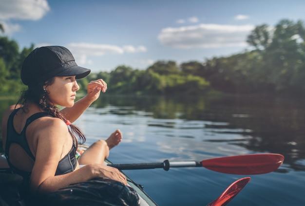 Sommerferien - rückansicht des kajakfahrens der jungen frau auf fluss.