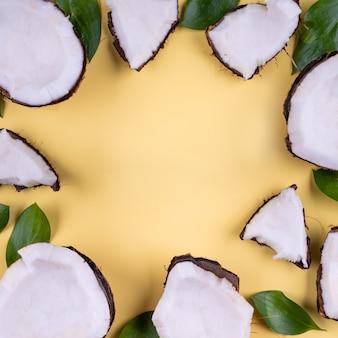 Sommerferien tropische wohnung legen mockup hintergrund grün blätter kokosnuss stück scheibe gelb auf gelb