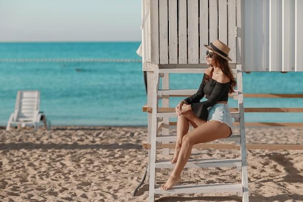 Sommerferien und ferienkonzept - mädchen in den denimkurzen hosen, die auf dem strand sitzen