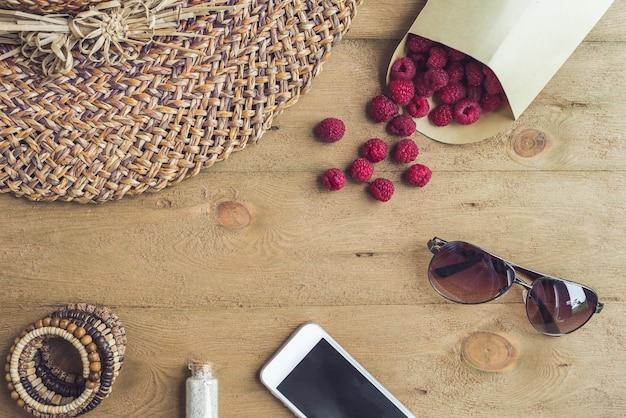 Sommerferien urlaub entspannung konzept himbeeren strohhut smartphone sonnenbrille von oben