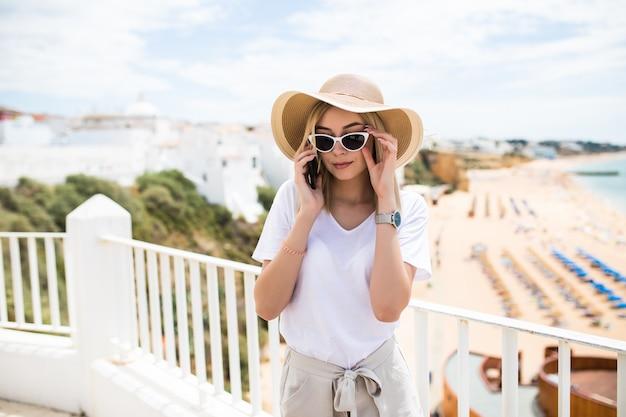 Sommerferienfrau, die handy-sms-nachricht draußen auf balkonterrasse verwendet