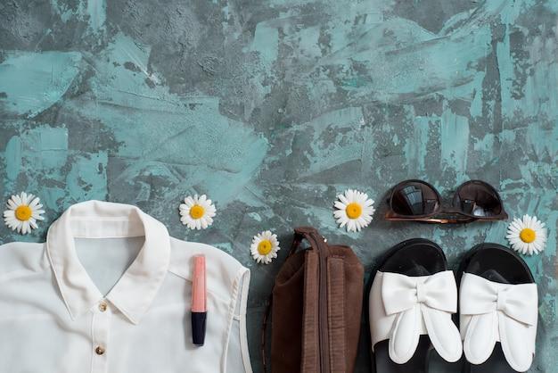 Sommerferienhintergrund, das zubehör der flachen lagestrandfrauen: strohhut, armbänder, ledersandalen, sonnenbrillen, perlen und seesterne auf blauer tabelle.