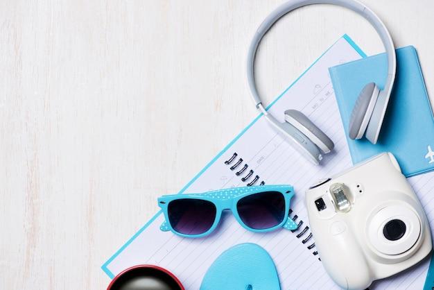 Sommerferienhintergrund, reise- und urlaubsartikel auf holztisch. ansicht von oben