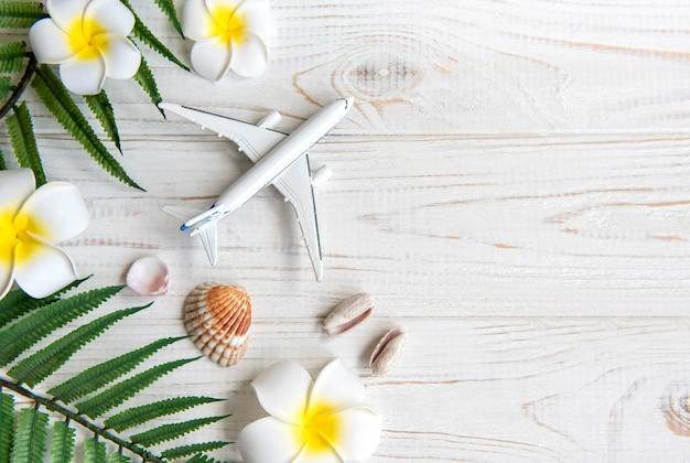 Sommerferienkonzept. frangipani, spielzeugflugzeug und muscheln auf weißem holzhintergrund