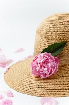 Sommerferienkonzept, geflochtener strohhut, rosa pfingstrosenblumen und blütenblätter auf weißer oberfläche, draufsicht. urlaubs- und reisebanner.
