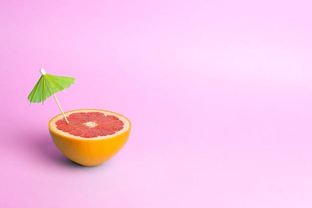 Sommerferienkonzept. grapefruit mit einem cocktailschirm auf einem farbigen hintergrund. tropen, sonne, strand, vitamine, obst, sommer und gute laune