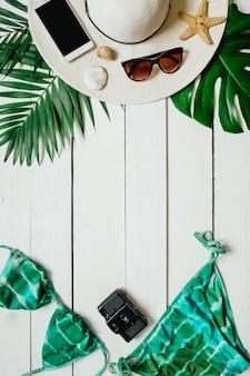 Sommerferienkonzept mit bikinianzug und zubehör auf weißem holztischhintergrund