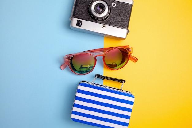 Sommerferienkonzept, reisekonzept mit tasche, kamera und brille auf blauem und gelbem hintergrund. flach liegen