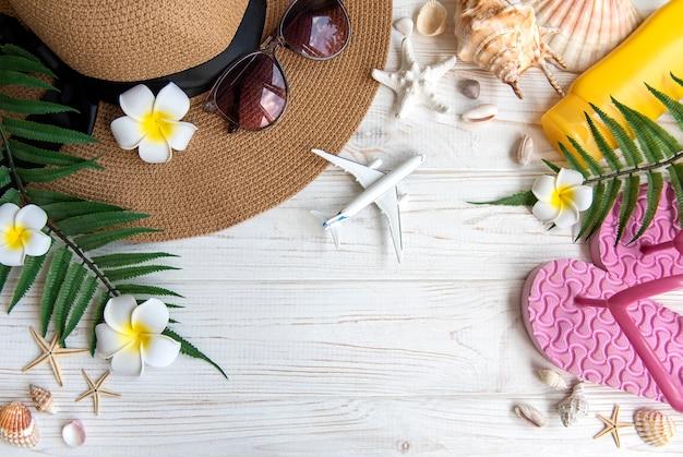 Sommerferienkonzept. strohhut und strandzubehör mit muscheln und seesternen auf weißem holzhintergrund