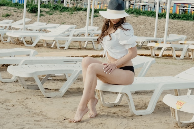 Sommerferienmodekonzept - bräunende frau mit sonnenhut am strand in weißer bluse und schwarzem bikini. mädchen im hut, der auf sonnenbank sitzt. sommerurlaub und reisen