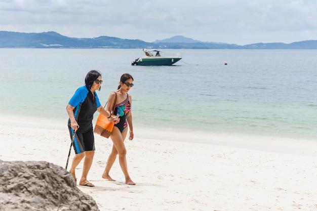 Sommerferientochter mit alter mutter, die zusammen auf tropischem strand geht.