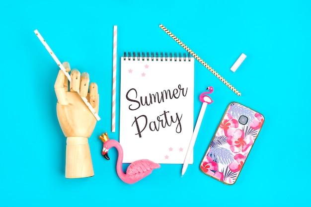 Sommerfestnotizbuch, stift, flamingofigur, smartphone, hölzerne hand halten trinkpapierstrohhalme auf blauem hintergrund