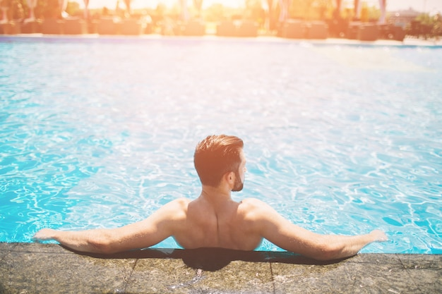 Sommerfoto des muskulösen lächelnden mannes im schwimmbad. glückliches männliches modell im wasser in den sommerferien.