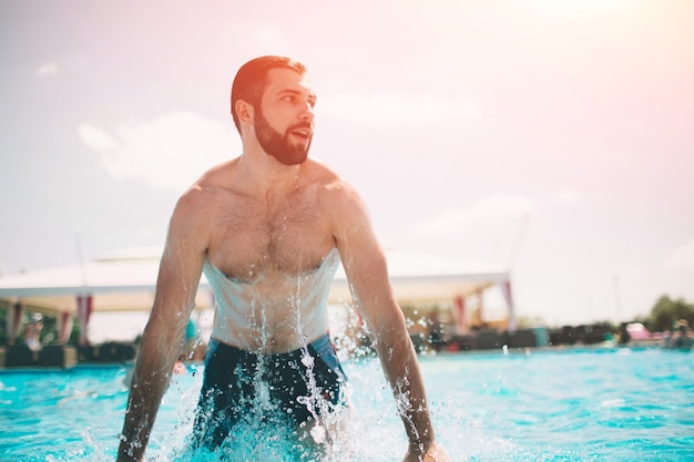 Sommerfoto des muskulösen lächelnden mannes im schwimmbad