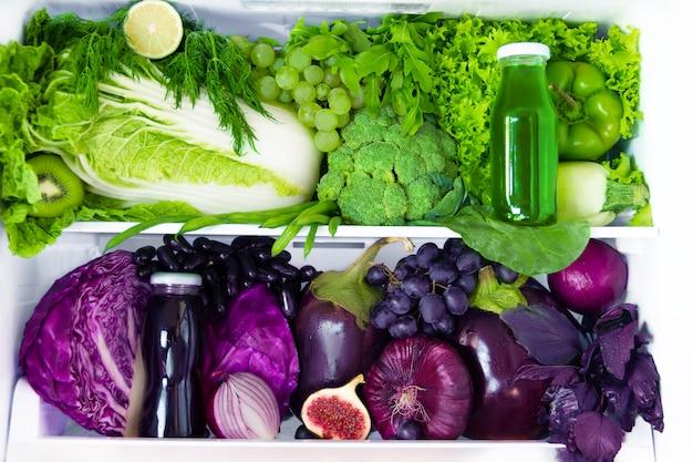 Sommerfrisches bio-gesundes rohes antioxidans grünes und violettes essen, gemüse, obst und säfte in veganem vegetarischem in geöffnetem vollem kühlschrank mit vitaminen. konzept für gesunde ernährung, ernährung und lebensstil.
