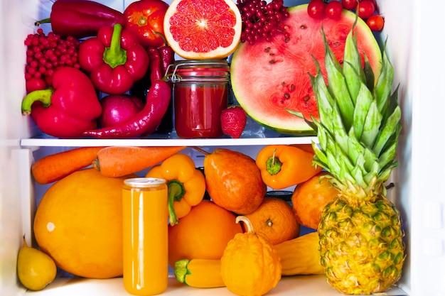 Sommerfrisches biologisches gesundes rohes antioxidans rotes und orange essen, gemüse, obst und säfte in veganem vegetarischem in geöffnetem vollem kühlschrank der vitamine. konzept für gesunde ernährung, ernährung und lebensstil.