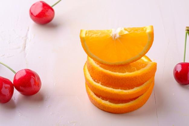 Sommerfruchtkirschen mit gestapelten orangen auf weißer hintergrundwinkelansicht