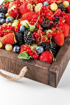 Sommerfrüchte und beeren. 6 arten von rohen bio-bauer beeren himbeeren brombeeren heidelbeeren erdbeeren rote johannisbeeren stachelbeeren. weiße tablettbox aus holz.