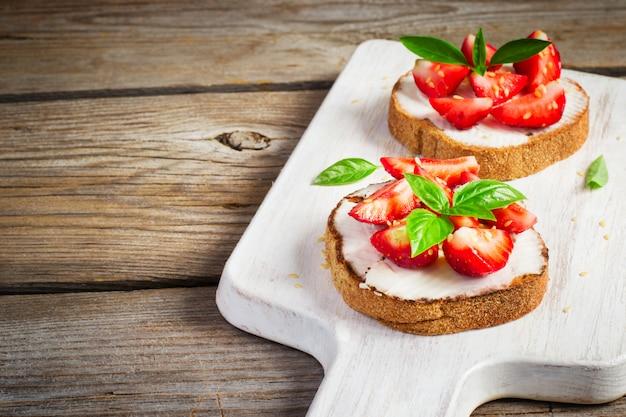 Sommerfrühstücksbruschetta mit erdbeeren, basilikum und häuschen